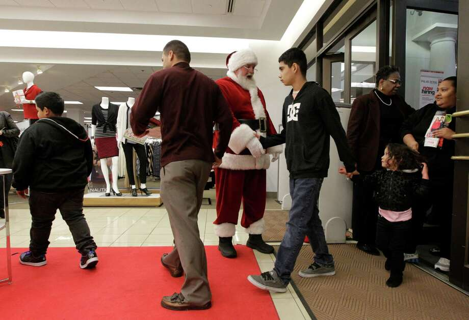 Santa welcomes shoppers as they walk into the Palais Royal at the Meyerland shopping center on Thursday, Nov. 28, 2013, in Houston. Photo: J. Patric Schneider, For The Chronicle / © 2013 Houston Chronicle