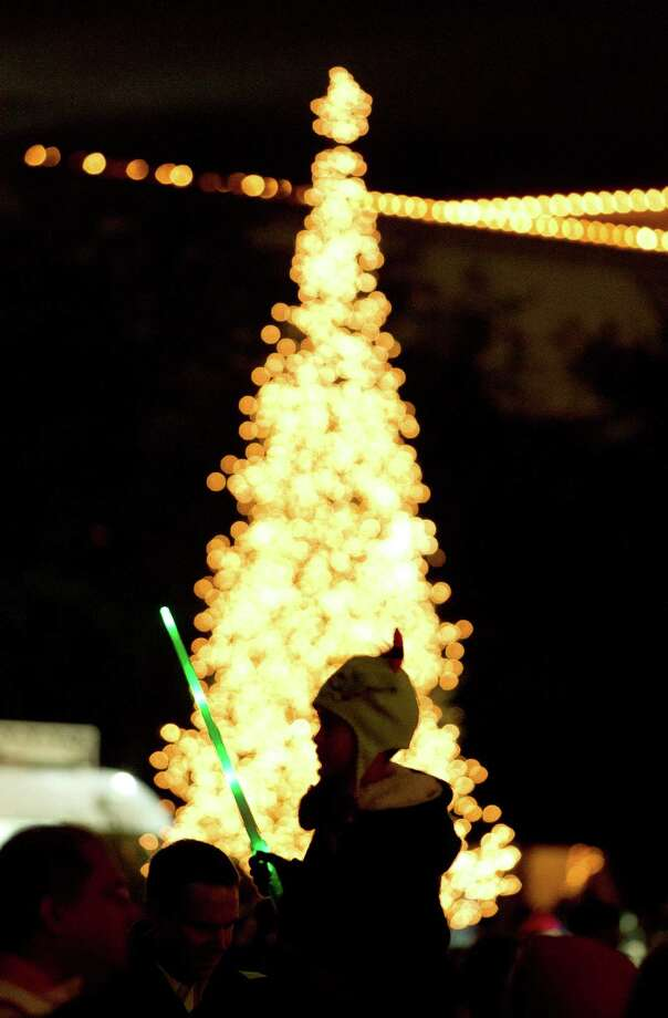 A young boy with a light sword joined thousands celebrating the holiday season during the 28th Annual Uptown Houston Holiday Lighting on the 2000 block of Post Oak Boulevard Thursday, Nov. 28, 2013, in Houston.  More than a half-million lights on 80 trees were lit on the tree-lined street along with festively lit  balconies, buildings and rooftops. The evening event featured holiday music, performances, a fireworks display and a visit from Santa. Photo: Johnny Hanson, Houston Chronicle / Houston Chronicle