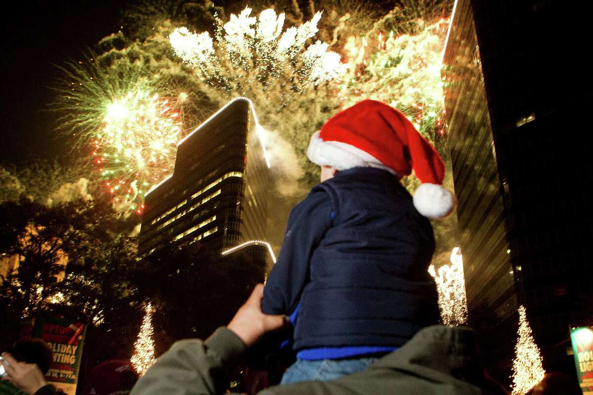 Sitting on the shoulders of his father, Sergio Martinez, of Mexico City, Matias Martinez, 3, watches the firework display during the 28th Annual Uptown Houston Holiday Lighting on the 2000 block of Post Oak Boulevard Thursday, Nov. 28, 2013, in Houston. More than a half-million lights on 80 trees were lit on the tree-lined street along with festively lit balconies, buildings and rooftops. The evening event featured holiday music, performances, and a visit from Santa.