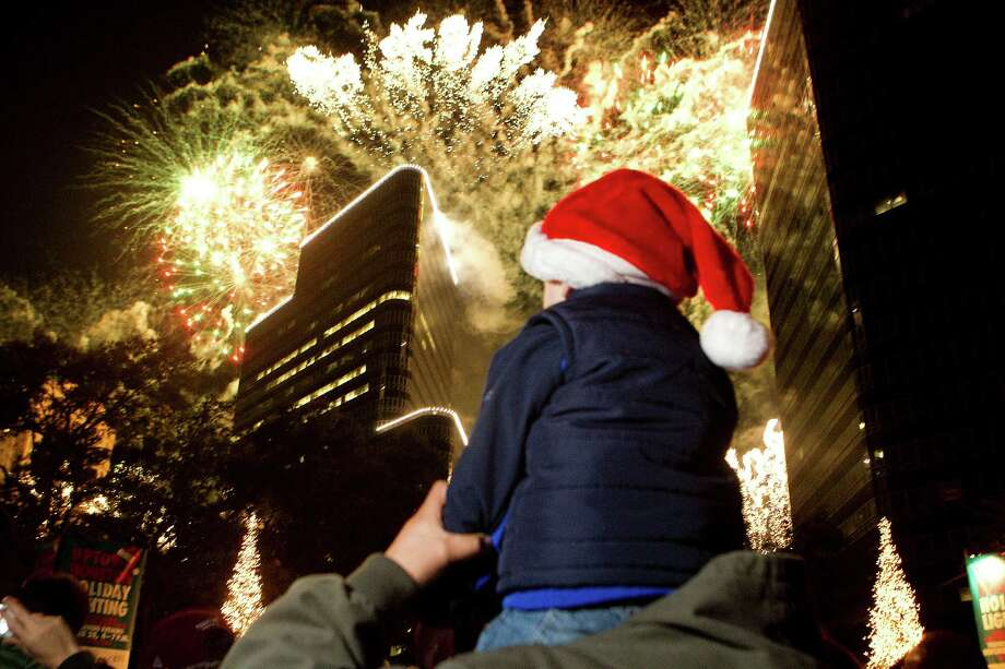 Sitting on the shoulders of his father, Sergio Martinez, of Mexico City, Matias Martinez, 3, watches the firework display during the 28th Annual Uptown Houston Holiday Lighting on the 2000 block of Post Oak Boulevard Thursday, Nov. 28, 2013, in Houston. 