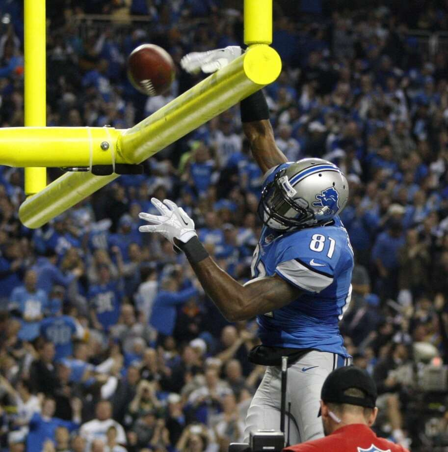 Calvin Johnson dunks the ball over the goal post after his third-quarter touchdown. Photo: Julian H. Gonzalez, McClatchy-Tribune News Service
