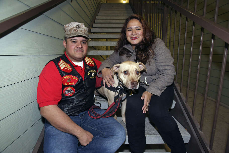 Juan Alonzo-Miranda, shown with his service dog, Goldie, and wife, Ilsa Alonzo, is suing his employer over his use of Goldie to cope with PTSD. Photo: Tom Reel / San Antonio Express-News