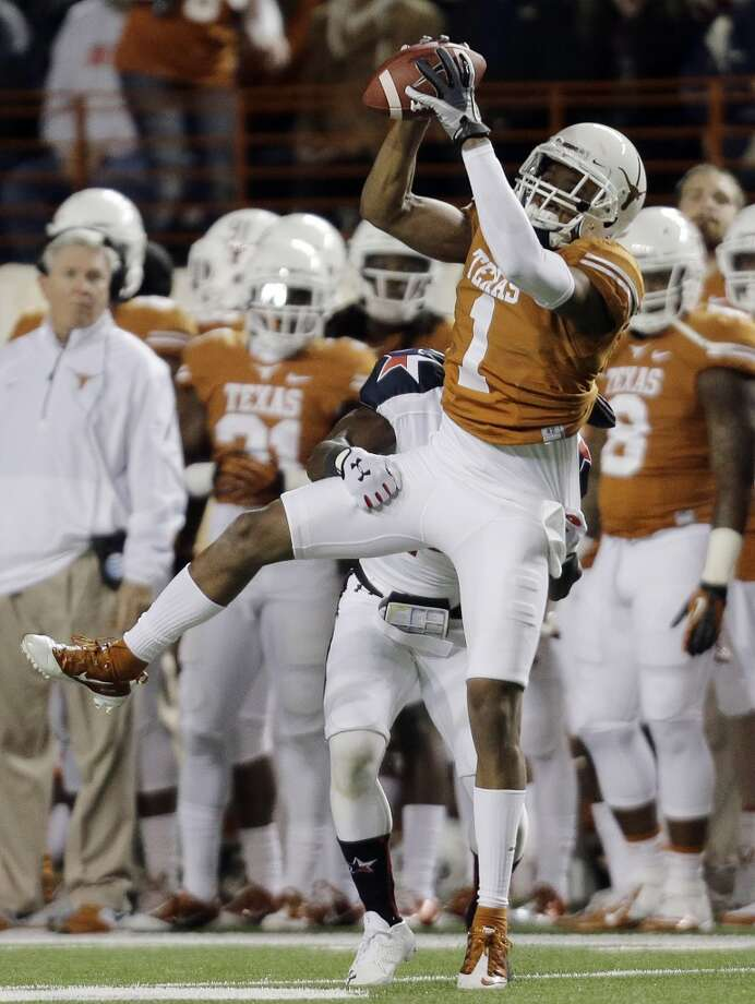 Texas' Mike Davis (1) catches a pass for a first down in front of Texas Tech's Bruce Jones during the first half of an NCAA college football game Thursday, Nov. 28, 2013, in Austin, Texas. Photo: Eric Gay, Associated Press