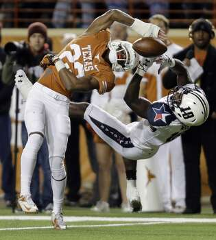 Texas' Carrington Byndom (23) breaks up a pass intended for Texas Tech's Eric Ward (18) during the first half of an NCAA college football game Thursday, Nov. 28, 2013, in Austin, Texas. Photo: Eric Gay, Associated Press