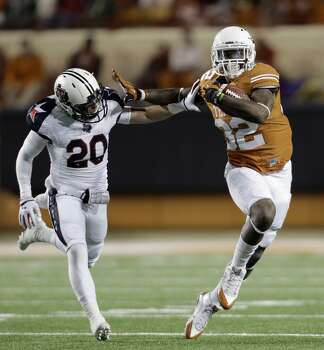 Texas' Johnathan Gray (32) runs past Texas Tech defender Tanner Jacobson (20) during the first half of an NCAA college football game Thursday, Nov. 28, 2013, in Austin, Texas. Photo: Eric Gay, Associated Press
