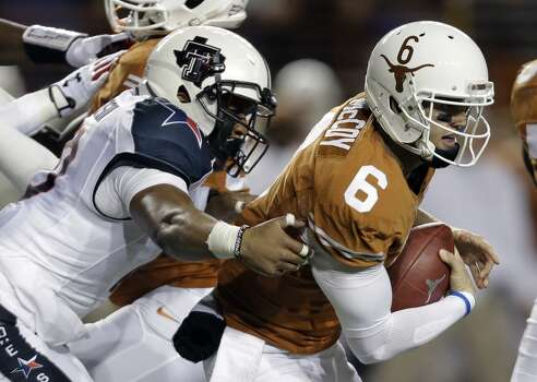Texas' Case McCoy (6) is pressured by Texas Tech's Pete Robertson, left, during the first half of an NCAA college football game Thursday, Nov. 28, 2013, in Austin, Texas. Photo: Eric Gay, Associated Press