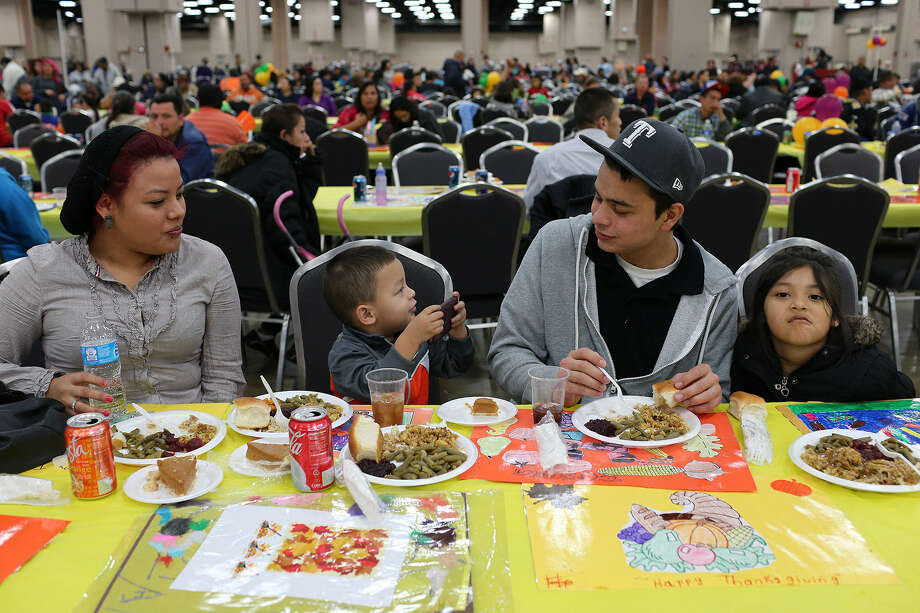 Three-year-old Dominick Medina (second from left) takes photos of members of his family at the Raul Jimenez Thanksgiving Dinner. With him are Wendy Palacios (from left), Michael Palacios and Natasha Palacios. Photo: Photos By Jerry Lara / San Antonio Express-News