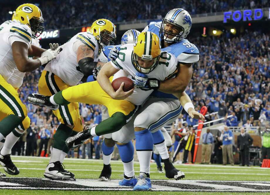 Lions defensive tackle Ndamukong Suh (right) tackles Packers QB Matt Flynn in the end zone for a safety in the third quarter. Detroit sacked Flynn seven times and scored 37 consecutive points Thursday in a rout. Photo: Paul Sancya / Associated Press
