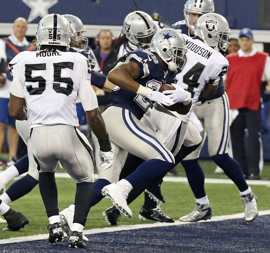 Cowboys running back DeMarco Murray finds his way through the Raiders' defense to reach the end zone during the first half in Arlington. Murray rushed for three touchdowns as Dallas rallied to grab sole possession of first place in the NFC East. Photo: Edward A. Ornelas / San Antonio Express-News