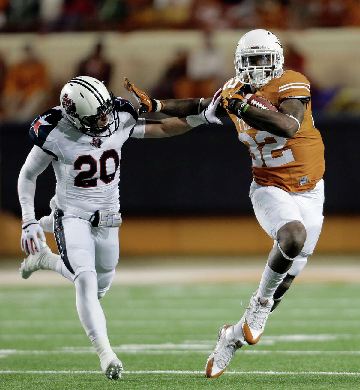 Texas' Johnathan Gray (32) runs past Texas Tech defender Tanner Jacobson (20) during the first half of an NCAA college football game Thursday, Nov. 28, 2013, in Austin, Texas. (AP Photo/Eric Gay)