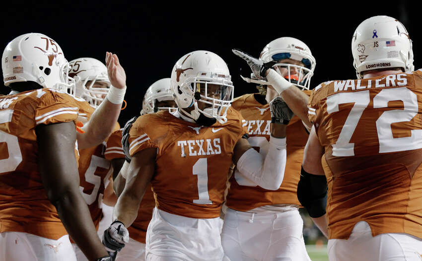 Texas' Mike Davis (1) is congratulated by teammates after he scored a touchdown against Texas Tech during the second half of an NCAA college football game, Thursday, Nov. 28, 2013, in Austin, Texas. (AP Photo/Eric Gay)
