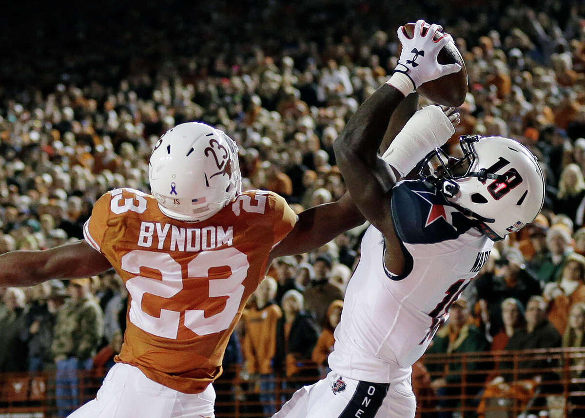 Texas Tech's Eric Ward (18) tries to make a catch over Texas defender Carrington Byndom (23) during the first half of an NCAA college football game Thursday, Nov. 28, 2013, in Austin, Texas. The pass was incomplete. (AP Photo/Eric Gay)