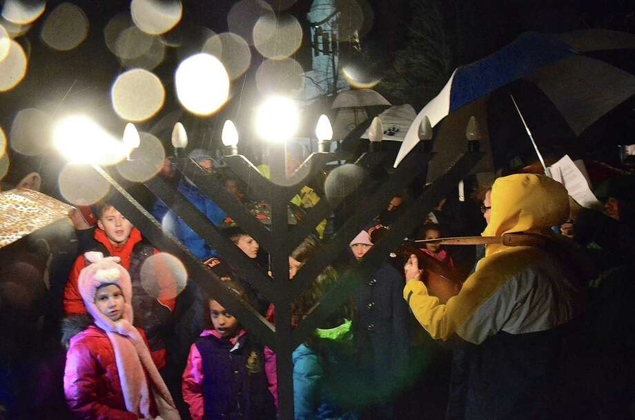New Canaan celebrated the first day of Hanukkah at the lighting the menorah, on a rainy Wednesday evening, November 27, 2013, on God's Acre in New Canaan, Conn. Photo: Jeanna Petersen Shepard / New Canaan News Freelance