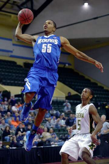 Memphis guard Geron Johnson (55) goes up to dunk the ball in front of Siena guard Evan Hymes (5) dur