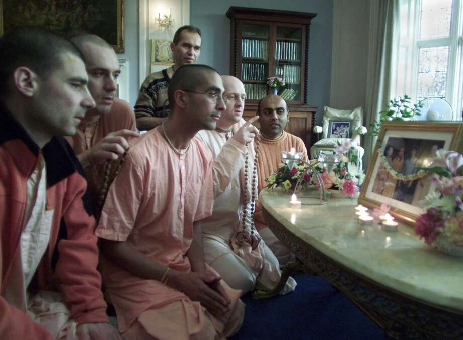 Hare Krishna devotees pray for the soul of late devotee George Harrison at a shrine set up for him in the Hare Krishna Temple,  Letchmore Heath, England, Saturday, Dec.1, 2001. Harrison, the former Beatles guitarist who died in the United States Thursday, donated the Letchmore temple to the Hare Krishna. Photograph, right, shows left to right, the founder of the Hare Krishna Srila Prabhupada, Harrison's first wife Patti Boyd, Harrison, and devotee Dhananjaya. (AP Photo/Max Nash) Photo: AP