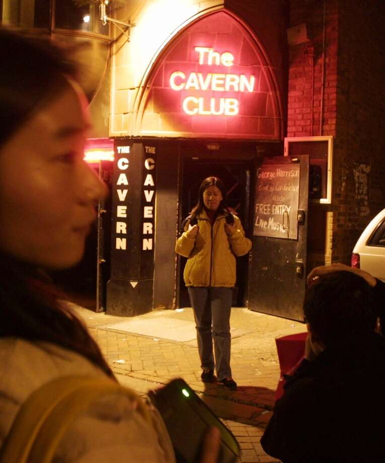 Japanese tourists take each others photograph outside the Cavern Club in Liverpool Saturday Dec. 1, 2001, where the Beatles played prior to their worldwide fame in the early 1960's.  Former Beatle George Harrison died of cancer in Los Angeles Thursday Nov. 29.  (AP Photo/Alastair Grant) Photo: AP