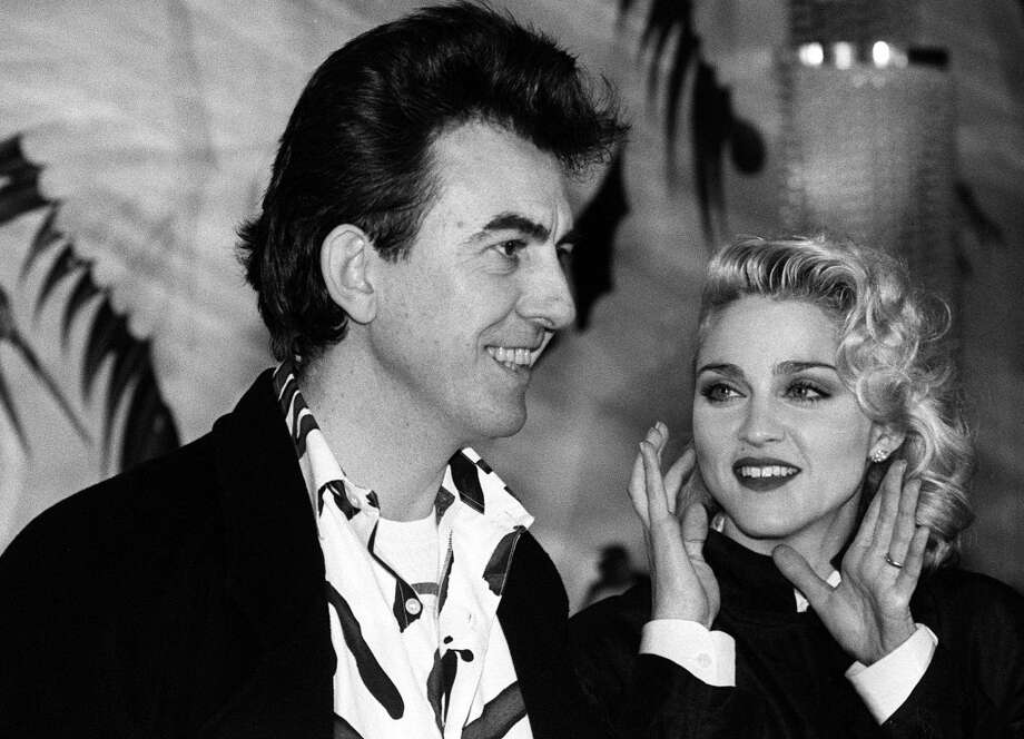 "In London in this March 6, 1986 file photo American singer Madonna claps as she stands with former Beatle George Harrison, executive producer of Handmade Films whose company produced ""Shanghai Surprise"" which stars Madonna and Sean Penn. Harrison died Thursday Nov. 29, 2001 at a friend's Los Angeles home following a battle with cancer. He was 58. (AP Photo/PA) UNITED KINGDOM OUT: MAGAZINES OUT: NO SALES: Photo: AP"