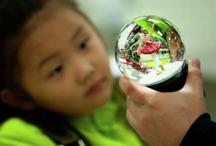 Long Yuan shows his daughter Ziwen Yuan, 5 a snow globe during Black Friday, Nov. 29, 2013, in Houston. Photo: Cody Duty, Houston Chronicle / © 2013 Houston Chronicle