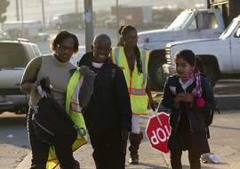 Uzuri Pease Green (left) walks children to school including Brianna Aragon (right), 7 years old, on Dakota St. in San Francisco, Calif., on Monday, November 25, 2013.  Her daughter Urell Pease (back, middle) also helps guide students during the walking school bus, created to help the children get to school.