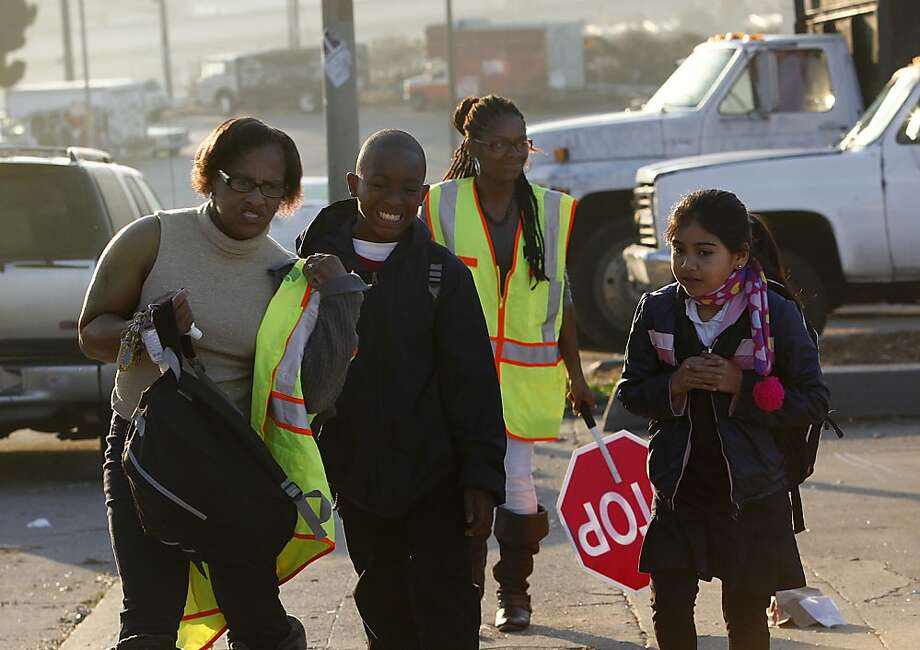 Uzuri Pease-Green (left) and her daughter, monitor Urell Pease, knock on doors to pick up children and walk them safely to school in San Francisco. Photo: Liz Hafalia, Chronicle