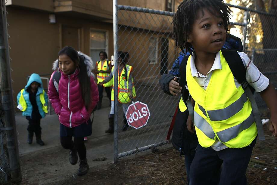 Romeo Robb (right), 5, joins the walking school bus organized by Urell Pease (holding stop sign) and her mother, Uzuri Pease-Greene (rear). Photo: Liz Hafalia, Chronicle