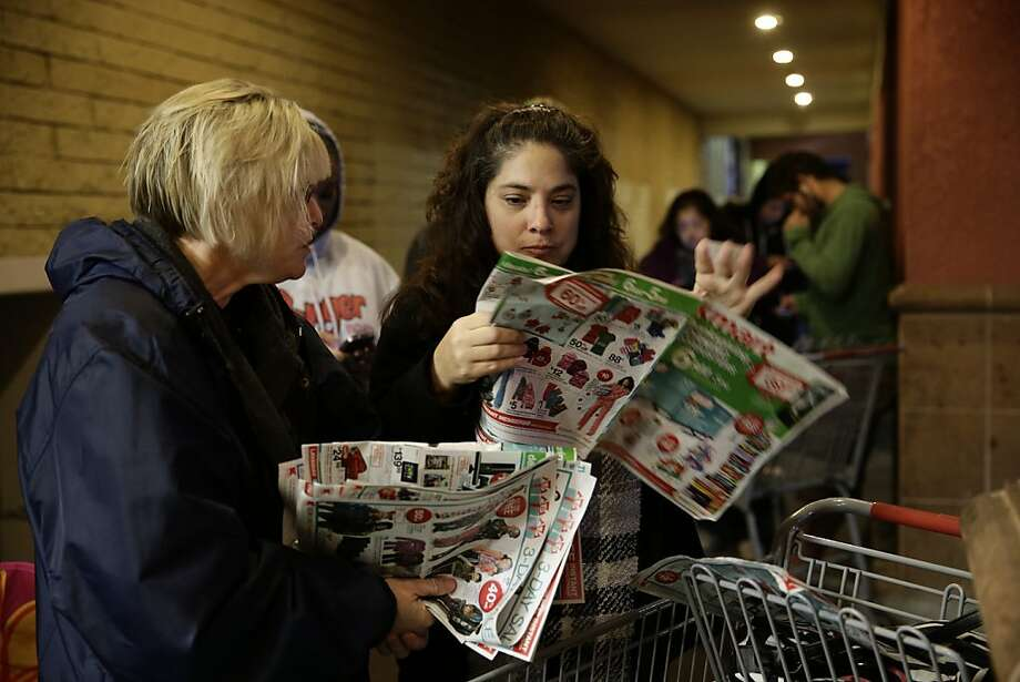Katie Stroh (left) and Gretchen Burkhardt look over sales ads while waiting outside a Kmart store in Anaheim on Thanksgiving Day. Photo: Jae C. Hong, Associated Press
