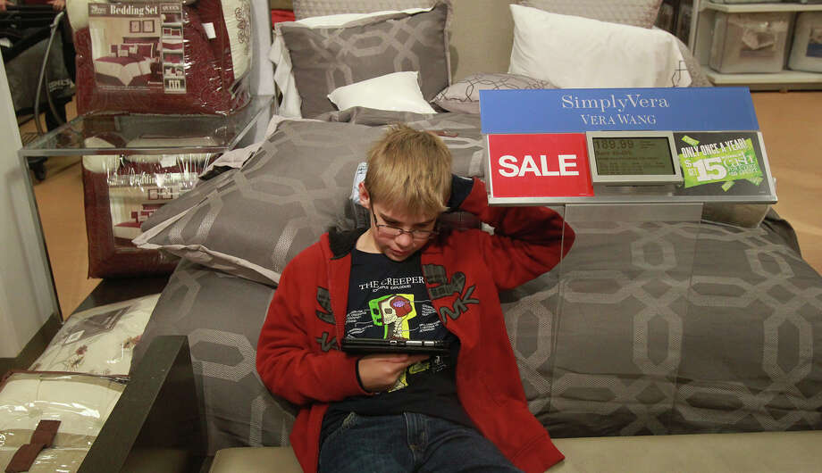 Dylan Frail,12, gets comfortable while waiting for his mother Cheryl Frail who was shopping at Kohl's at 11,781 Bandera Road Black Friday November 29, 2013. Photo: JOHN DAVENPORT, John Davenport / San Antonio Express-News / ©San Antonio Express-News/Photo may be sold to the public