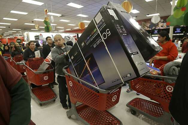 A man pushes two televisions in a shopping cart at a Target store in Colma, Calif., on Thanksgiving Day, Thursday, Nov. 28, 2013. Instead of waiting for Black Friday, which is typically the year's biggest shopping day, more than a dozen major retailers opened on Thanksgiving day this year. (AP Photo/Jeff Chiu) Photo: Jeff Chiu, Associated Press