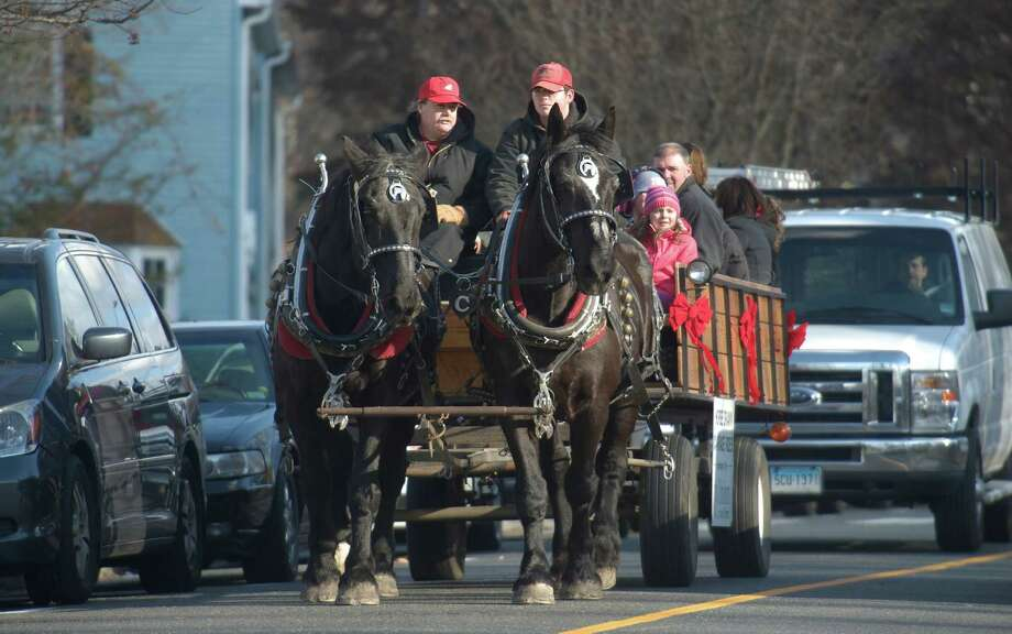 Bryan Clark, left, and his nephew Noah Clark, from Maple View Farm in Orange Conn, guide brothers Jake and Elwood down School Street, in Bethel, Conn. They were giving horse drawn carriage rides as part of Bethel WinterFest on Friday November 29, 2013. The rides were  sponsored by Union Savings Bank. Photo: H John Voorhees III / The News-Times Freelance