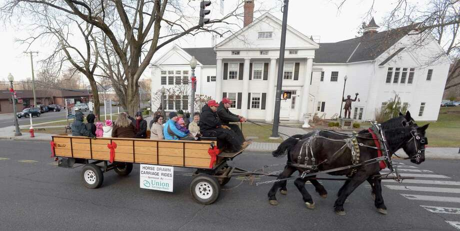 Bryan Clark, left, and his nephew Noah Clark, from Maple View Farm in Orange Conn, guide brothers Jake and Elwood down Greenwood Avenue in Bethel, Conn. They were giving horse drawn carriage rides as part of Bethel WinterFest on Friday November 29, 2013. The rides were  sponsored by Union Savings Bank. Photo: H John Voorhees III / The News-Times Freelance