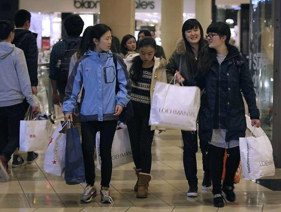Shoppers carry bags filled with Black Friday bargains as they search for more gift items on sale at the Westfield SF Centre, where the holiday shopping season is in full swing, in San Francisco, Calif. on Friday, Nov. 29, 2013. Photo: Paul Chinn, The Chronicle