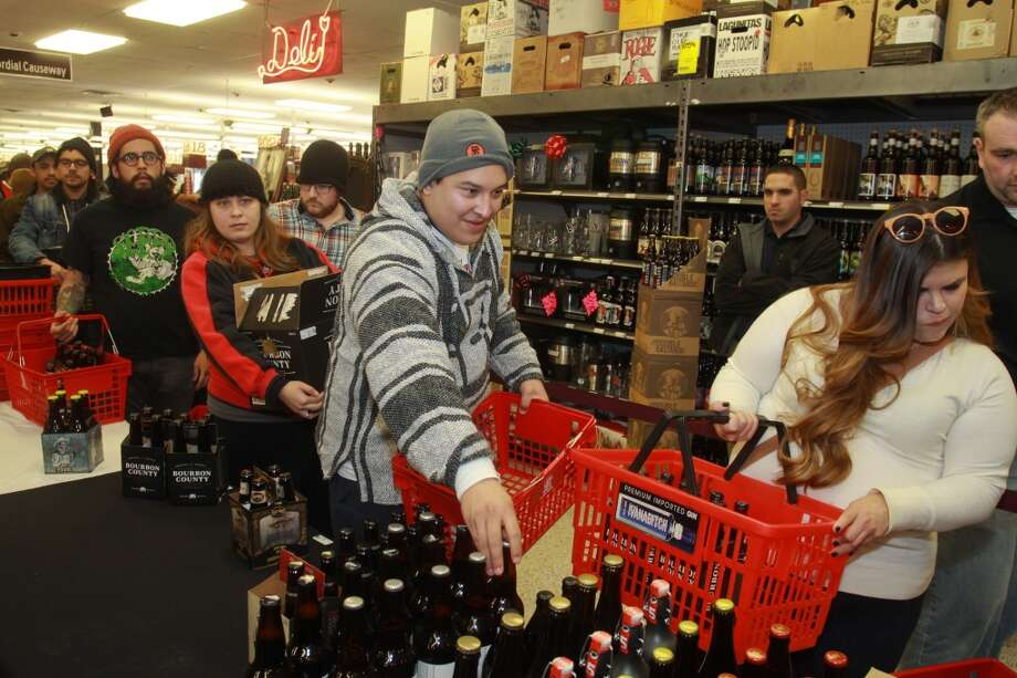 Jessica and Jesse Rios, from left, and Melissa Vega in line at Spec's Wines, Spirits and Beer on Smith Street to purchase a beer Spec's was releasing a first-time-in-Texas beer called Bourbon County Brand Stout, from Goose Island Beer Co. Photo: Gary Fountain, For The Chronicle