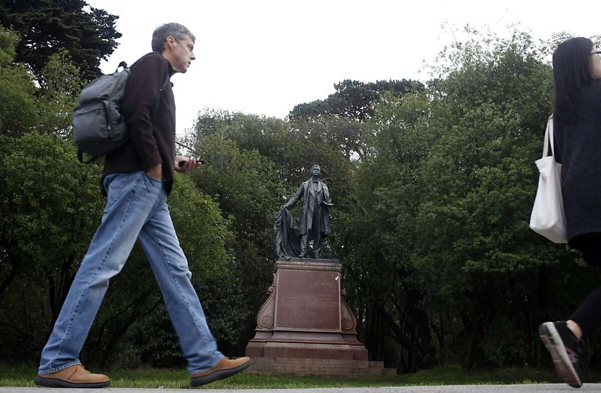 People walk past the statue of Thomas Starr King, a 19th century Unitarian minister, in Golden Gate Park, Tuesday November 26, 2013, in San Francisco, Calif.