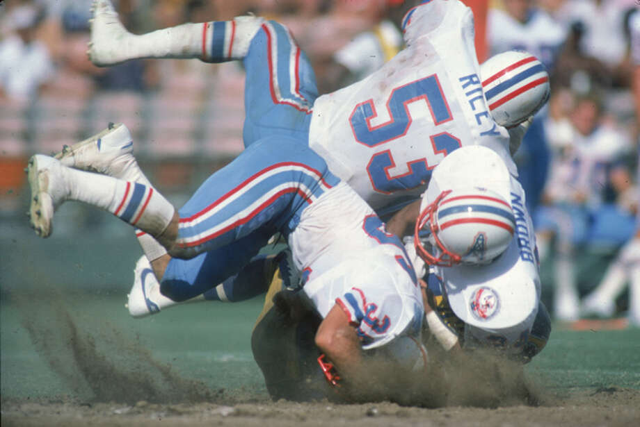 Linebacker Avon Riley #53 of the Houston Oilers teams up with cornerback Steve Brown #24 to stop a San Diego Chargers player at Jack Murphy Stadium on September 16, 1984 in San Diego, California. The Chargers defeated the Oilers 31-14. (Photo by Rob Brown/Getty Images) Photo: Rob Brown, NFL / 1984 Rob Brown
