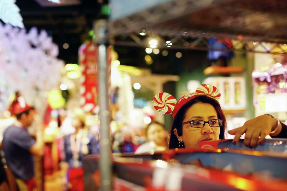 "Disney store employee Silvia Callegas stocks shelves, Friday, November 29, 2013 during The Disney Store's Black Friday ""magical sale"" at the Galleria mall in Houston, Texas. The sale featured 20% off every item in the store along with other deals. (TODD SPOTH FOR THE CHRONICLE) Photo: © TODD SPOTH, 2013 / © TODD SPOTH, 2013"