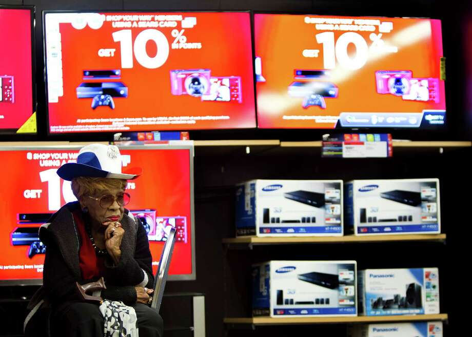 Edith Clark of Houston sits by televisions on sale while her cousin shops for a small television on sale for her, Friday, Nov. 29, 2013, in Houston. Photo: Marie D. De Jesus, Houston Chronicle / © 2013 Houston Chronicle