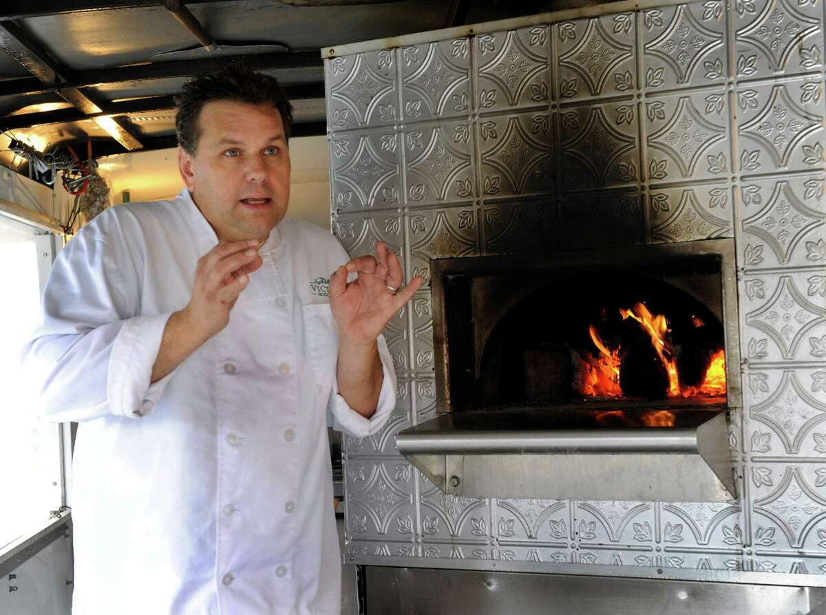 Bruce Lyon, 49, of Danbury, Conn., is the owner of Victoria's Wood Fired Pizza Catering. Wednesday he photographed speaking in front of a wood stove in his vending cart, Nov. 27, 2013.