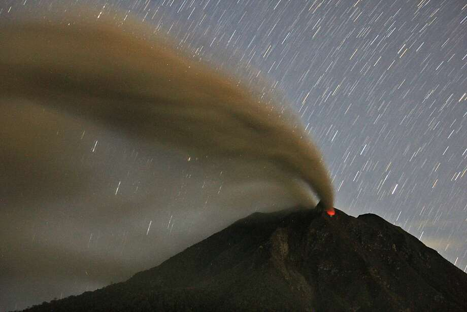 Star trails fill the sky over erupting Mount Sinabung in this long-exposure image taken from Tiga Pancur, North Sumatra. Indonesian authorities raised the alert status of the volcano to the highest level this week. Photo: Binsar Bakkara, Associated Press