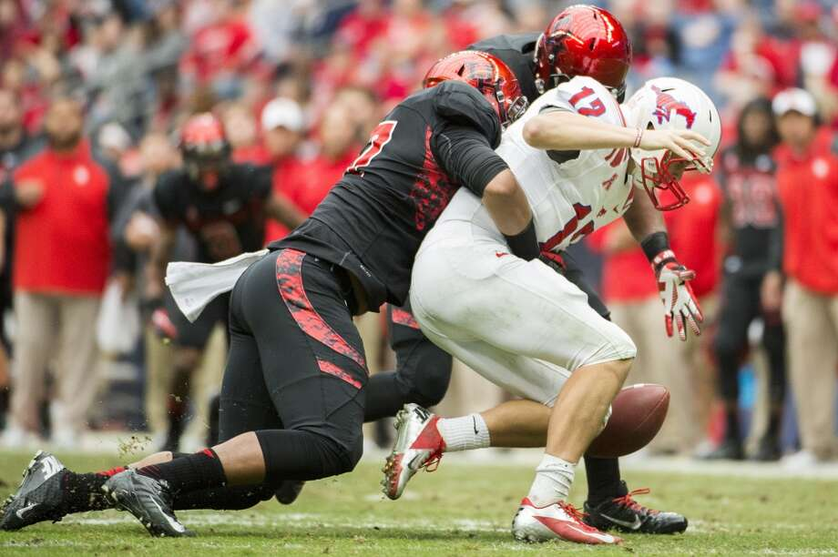 Eric Braswell of the Cougars sacks and forces a fumble against SMU quarterback Neal Burcham. Photo: Smiley N. Pool, Houston Chronicle