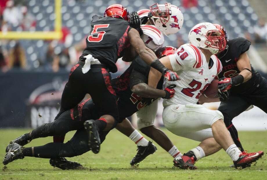 UH linebacker Derrick Mathews tackles Nate Halverson of SMU. Photo: Smiley N. Pool, Houston Chronicle