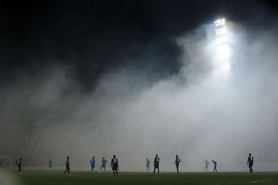Cloudy on the pitch: Bordeaux and Frankfurt players wait for the smoke to clear to begin play in a UEFA Europa League Group F qualifier at Chaban-Delmas Stadium in Bordeaux,  France. Photo: Nicolas Tucat, AFP/Getty Images