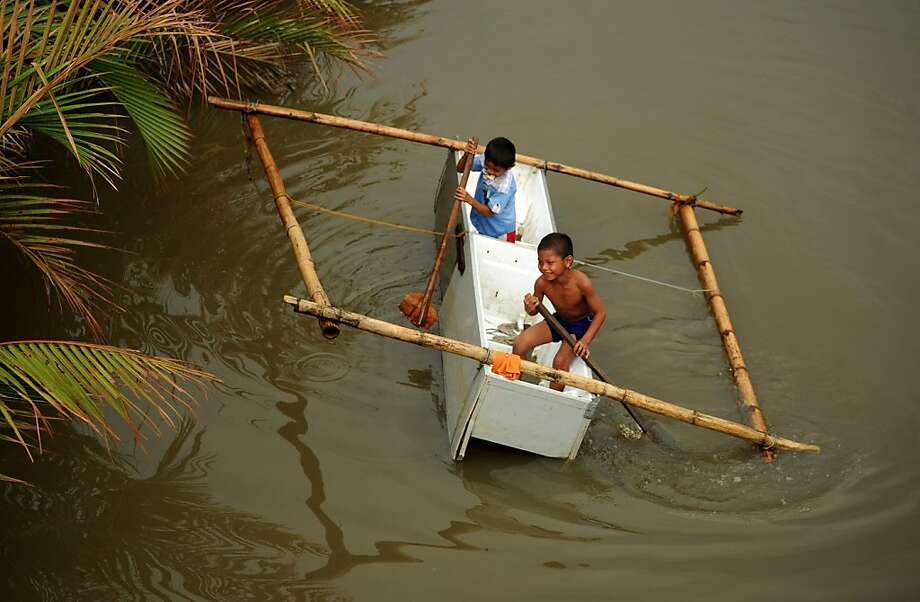 Canoeing in a Whirlpool:In Basay, Philippines, kids paddle an old refrigerator turned outrigger down a river. Photo: Noel Celis, AFP/Getty Images
