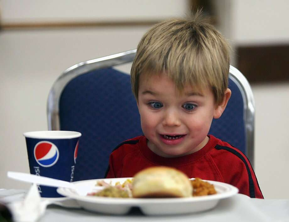 Some people just don't like yams: Three-year-old Dan Farley eyes his Thanksgiving dinner with fear and loathing at the Sons of Norway in Bremerton, Wash. Olympic High School DECA students served the outreach meal. Photo: Larry Steagall, Associated Press