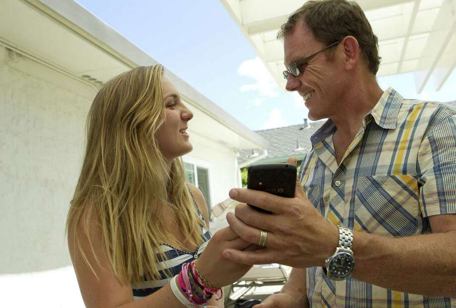 Will MacDonald, right, and his daughter Kendall MacDonald, 15, are amused by a photo they just posted onto Instagram during a family birthday party in Sunnyvale, Calif., Aug. 25, 2013. (LiPo Ching/Bay Area News Group/MCT) ORG XMIT: 1146045 Photo: LiPo Ching / San Jose Mercury News