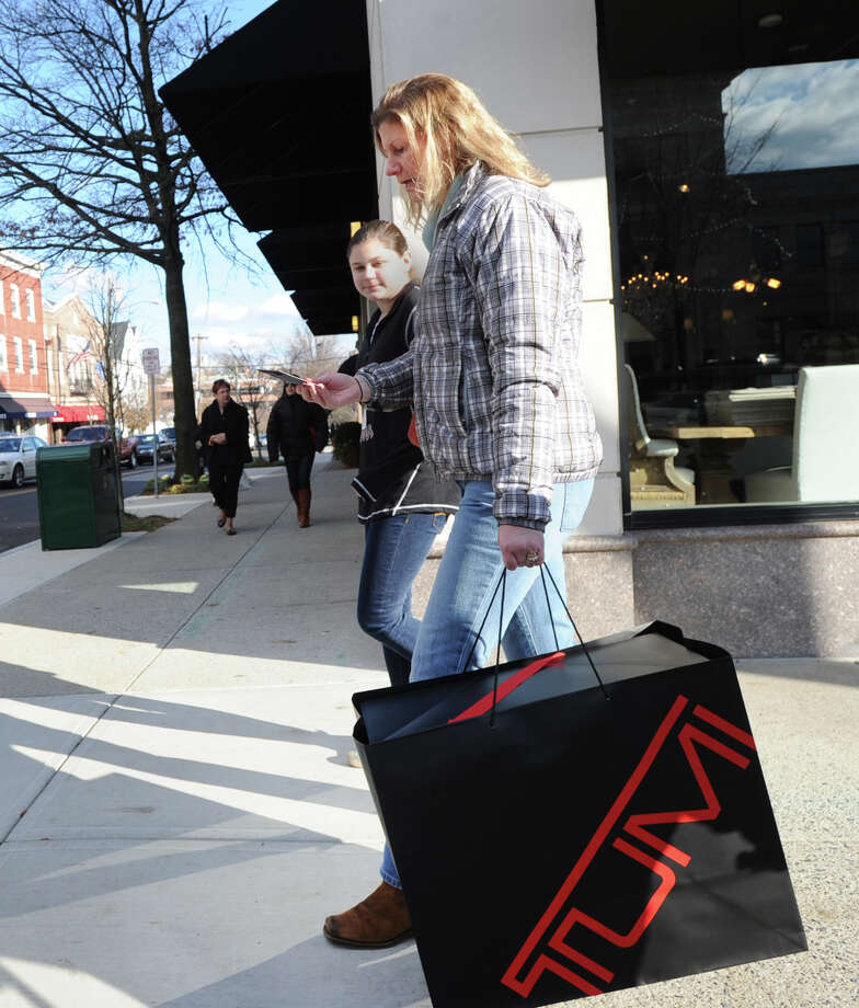 In foreground, Lisa Daur, of Greenwich, with her daughter, Phoebe Daur, 14, as the pair walk on Greenwich Avenue while shopping on Black Friday in Greenwich, Nov. 29, 2013. Lisa Daur said she was buying holdiay gifts but declined to say what they were and who they were for. Photo: Bob Luckey / Greenwich Time