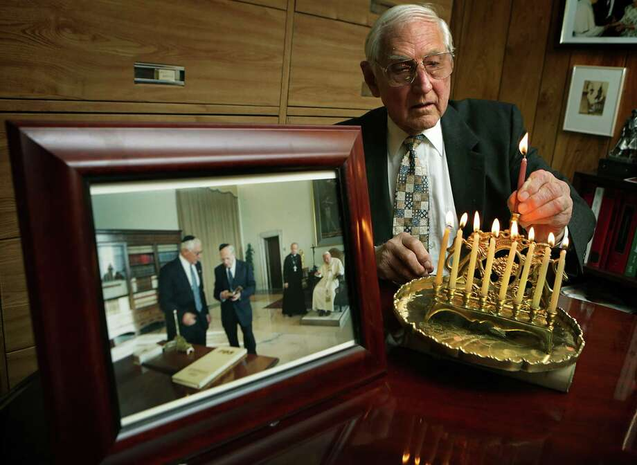 Bennett Feinsilber lights a menorah in his office next to his home, the same menorah he lighted with Pope John Paul II back in 2001, as seen in the photo. Tuesday, Nov. 26, 2013. Photo: BOB OWEN, San Antonio Express-News / © 2012 San Antonio Express-News