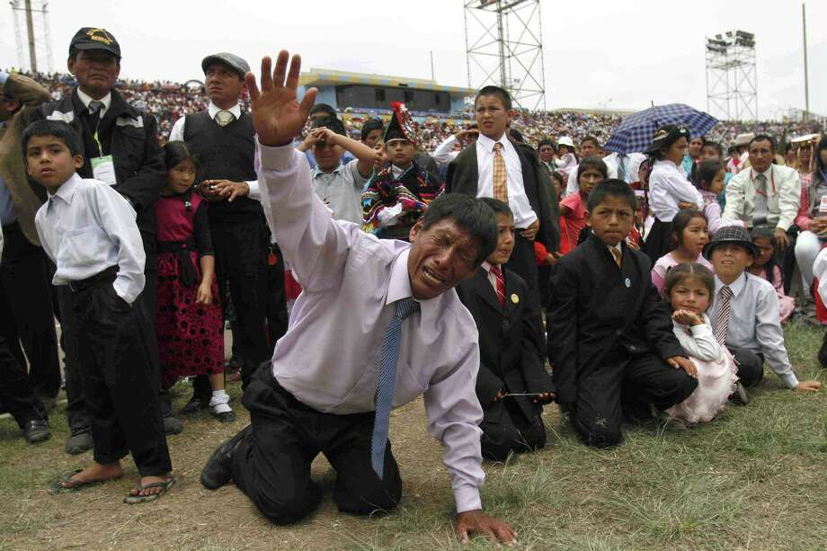 Jorge Mamani prays on his knees during a service at a San Marcos stadium that hosted the Worldwide Missionary Movement National Congress in Lima, Peru. Tens of thousands of evangelical Christians converged on Lima for a national congress. Photo: Photos By Karel Navarro Pando / Associated Press