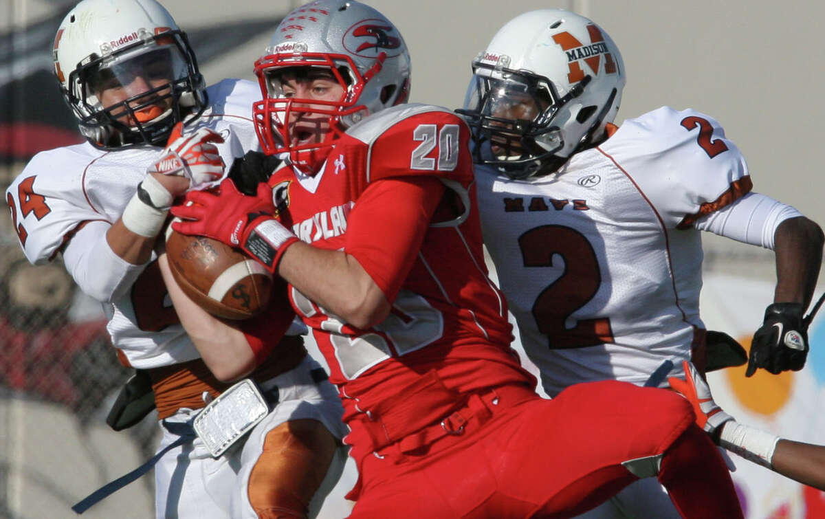 Madison's Jordan Gonzalez and Latrell Sledge defend Mission Sharyland's Brandon Garza in second quarter play during a third round playoffs game at Buccaneer Stadium in Corpus Christi on Friday, Nov. 29, 2013.