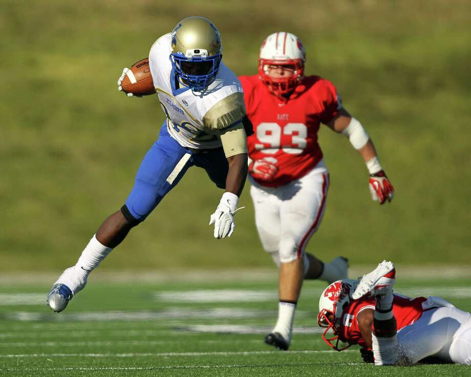 Elkins' Timothy Jackson, left, leaps past Katy's JoVanni Stewart during the second half of a high school football playoff game, Friday, November 29, 2013, at Tully Stadium in Houston. Photo: Eric Christian Smith, For The Chronicle