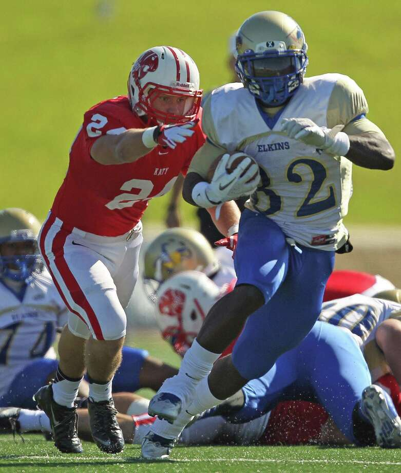 Elkins' Timothy Jackson, right, escapes the tackle of Katy's Jason Ellis during the first half of a high school football playoff game, Friday, November 29, 2013, at Tully Stadium in Houston. Photo: Eric Christian Smith, For The Chronicle